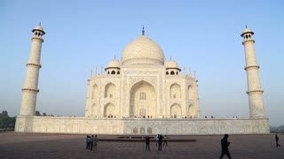 Taj Mahal front view, with people passing and blue sky in background.