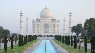 Taj Mahal front view, with tourists walking in garden.