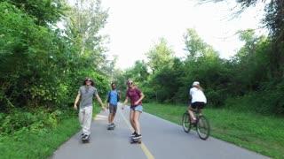 Three cool cheerful friends skateboarding