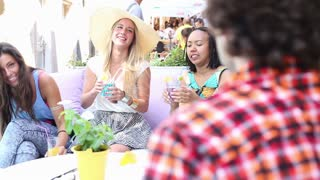 Three young, beautiful female friends having fun drinking cocktails and cheering with friends on terrace cafe on a summer day.