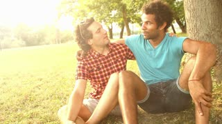 Three young men and women sitting on the grass while taking selfies and having fun in the park, graded brighter.