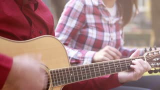 Tilt shot of beautiful young couple singing and playing guitar in park, graded