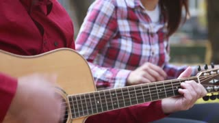 Tilt shot of beautiful young couple singing and playing guitar in park