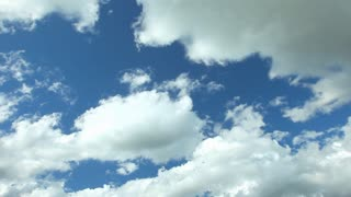 Timelapse of white fluffy clouds moving fast in the blue sky