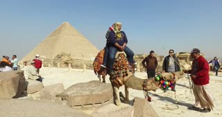 Tourist on a camel in front of pyramids of Giza