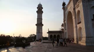Tourists in front of entrance to Taj Mahal at sunset.