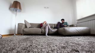 Tracking shot of couple on couch in living room