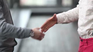 Two advertising executives shaking hands, close up on hands