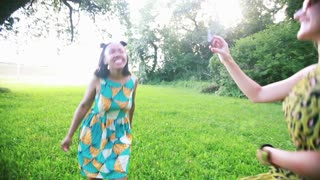 Two beautiful young women dancing together and having fun while taking selfies in the park.
