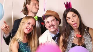 Two cute couples making funny faces in party photo booth
