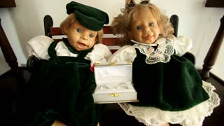 Two cute sitting dolls holding beautiful golden wedding ring