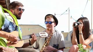 Two guys playing music at the party while girl taking photos and laughing
