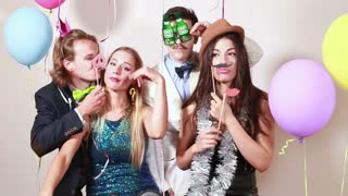 Two happy couples having a great time in photo booth