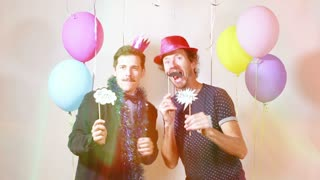Two happy men dancing with props in photo booth