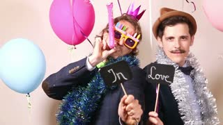 Two men holding sign in love and dancing in photo booth