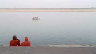 Two men sitting on stairs and watching boat sailing on Ganges river.