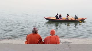 Two men sitting on stairs and watching boats sailing on Ganges river.