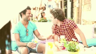 Two young, male friends having fun drinking cocktails and chatting with friends on terrace cafe in town in summer, graded warmer.