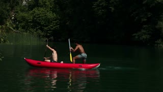 Two young male friends having fun riding canoe and splashing their female friends with paddles on the Mreznica river