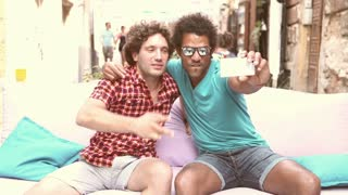 Two young men having fun while taking selfies in town, graded warmer.