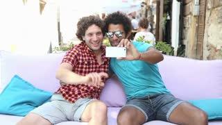 Two young men having fun while taking selfies in town.