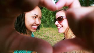 Two young women having fun while smiling and making heart shape with hands in the park.
