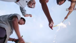 Under view of cheerful friends waving with firework candles
