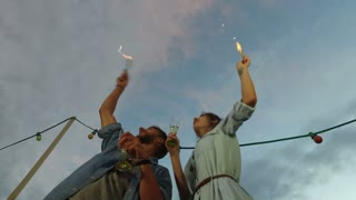 Under view of couple drinking champagne and waving with firework candles