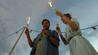 Under view of couple having fun waving with firework candles