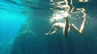 Underwater shot of couple swimming and diving in cave