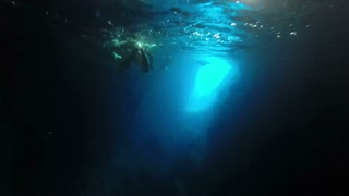 Underwater shot of people swimming in cave