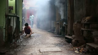 VARANASI, INDIA - 19 FEBRUARY 2015: Boy pouring water on smoky street in Varanasi while people pass by.
