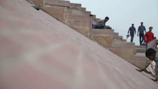 VARANASI, INDIA - 19 FEBRUARY 2015: Children climbing and sliding down the slope at dock of Ganges in Varanasi.