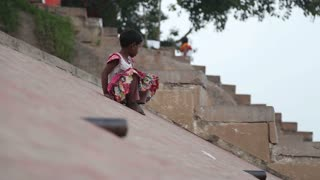 VARANASI, INDIA - 19 FEBRUARY 2015: Indian girl sliding down the slope on ghats of Ganges river in Varanasi.