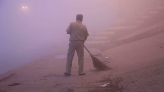 VARANASI, INDIA - 19 FEBRUARY 2015: Man brooming the dock of Ganges river in night time, with man passing.