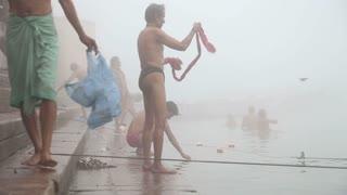 VARANASI, INDIA - 19 FEBRUARY 2015: Men bathing in foggy Ganges river in Varanasi.