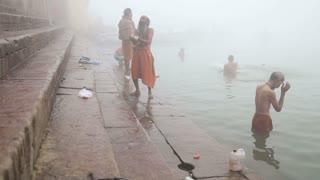 VARANASI, INDIA - 19 FEBRUARY 2015: Men praying and bathing on shore of foggy Ganges river in Varanasi.