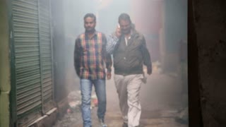 VARANASI, INDIA - 19 FEBRUARY 2015: Men walking down the smoky passage in Varanasi and talking on phone.