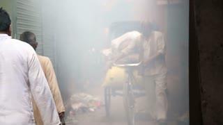 VARANASI, INDIA - 19 FEBRUARY 2015: People passing down the smoky passage in Varanasi.