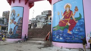 VARANASI, INDIA - 20 FEBRUARY 2015: Hindu deities on the pillars of street in Varanasi, with people passing by.
