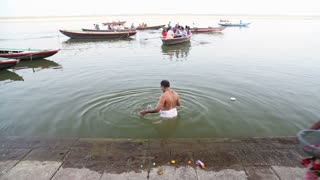 VARANASI, INDIA - 20 FEBRUARY 2015: Man bathing in Ganges while boat arrives to the shore.
