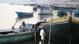 VARANASI, INDIA - 20 FEBRUARY 2015: Man laying on a boat anchored in bay of Ganges river in Varanasi .
