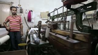 VARANASI, INDIA - 20 FEBRUARY 2015: Man standing by a working weaving machine in workshop in Varanasi.
