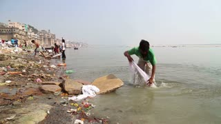 VARANASI, INDIA - 20 FEBRUARY 2015: Man washing laundry on shore of Ganges, with city in the background.