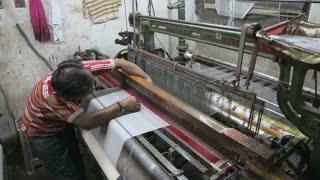 VARANASI, INDIA - 20 FEBRUARY 2015: Man working on weaving machine in workshop in Varanasi.