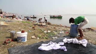 VARANASI, INDIA - 20 FEBRUARY 2015: People washing laundry on shore of Ganges, while boats sail through river.