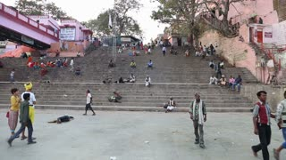 VARANASI, INDIA - 20 FEBRUARY 2015: View on stairs in Varanasi, with people sitting and passing in front.