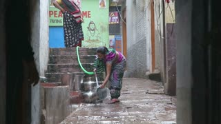 VARANASI, INDIA - 20 FEBRUARY 2015: Woman filling a bucket with water at street in Varanasi.