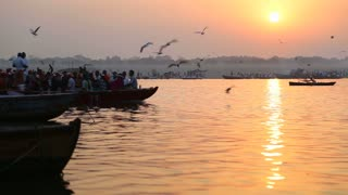 VARANASI, INDIA - 22 FEBRUARY 2015: Boat full of people sailing through Ganges at sunset, with birds flying above.
