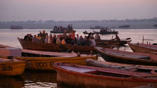 VARANASI, INDIA - 22 FEBRUARY 2015: Boats full of people sailing through river Ganges at sunset.